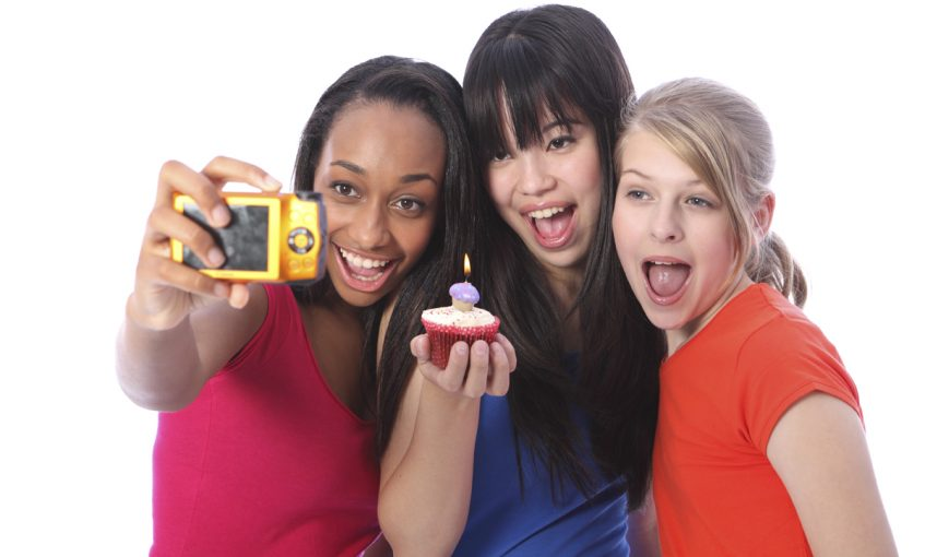 Birthday celebration photograph with candle on cakes for three beautiful young teenager girl friends a blonde caucasian, an oriental Japanese and an African American girl holding the camera.